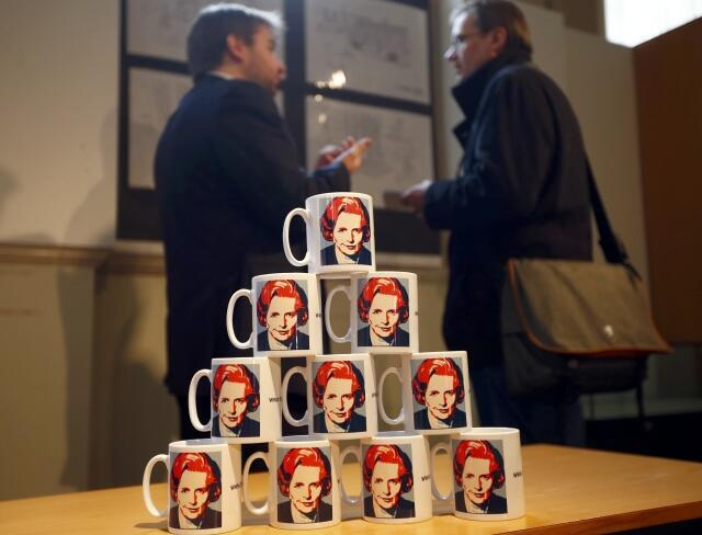 Men speak behind a display of mugs depicting former British prime minister Margaret Thatcher in a museum in Grantham