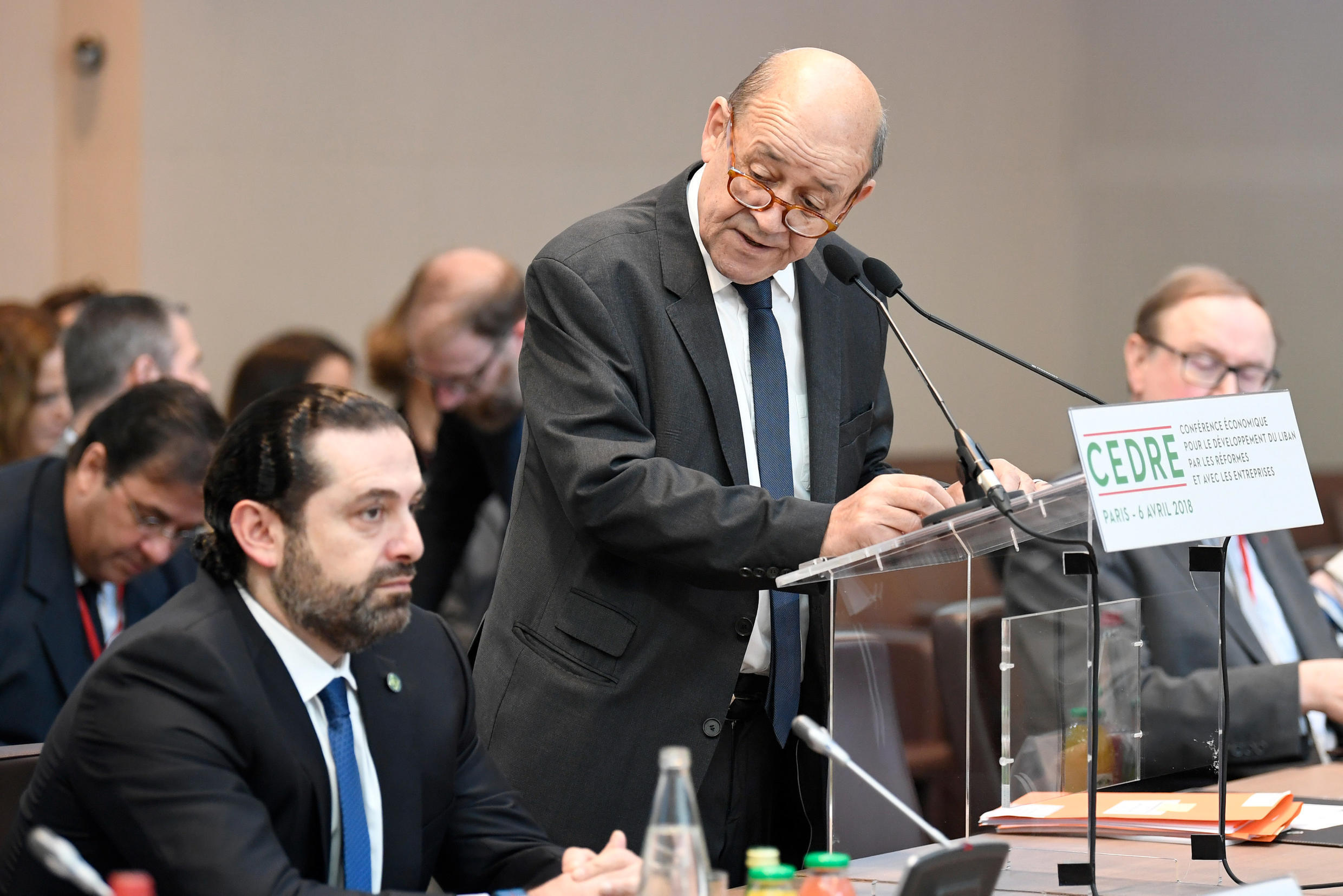 French Foreign Minister Jean-Yves Le Drian delivers his opening speech as Lebanese Prime Minister Saad Hariri at the Cedre conference