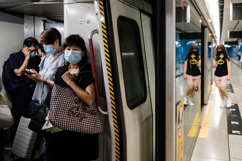 Moradores de Hong Kong usando máscaras no transporte público, enquanto número de novas contaminações bate recorde.