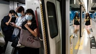 "Commuters wear face masks on a metro train in Hong Kong. The city's leader says coronavirus is running ""out of control"" after a daily record number of new cases"
