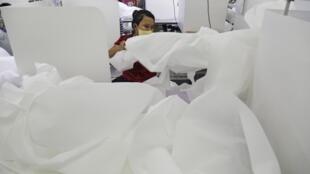 Dans une usine de textile de Rangoon, le 8 mai 2020. Des employés sont chargés de fabriquer des combinaisons pour le personnel de santé.