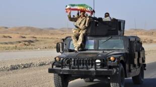 一名库尔德战士举着库尔德斯坦的旗。