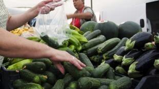Mulher compra pepinos, apesar das advertências sanitárias, em feira na Espanha.