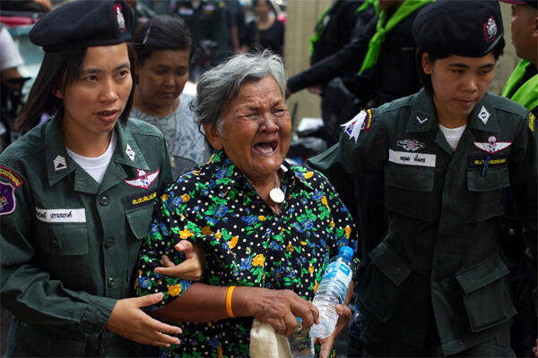 A woman weeps while being escorted out of a temple where she was seeking refuge in Bangkok