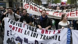 "Protestors in Paris march behind a banner reading: ""United against the labour law"", 17 May 2016."