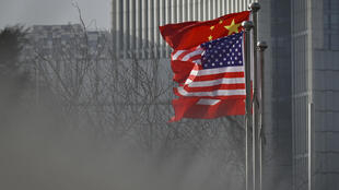 Chinese and US national flags flutter at the entrance of an office in Beijing in January 2020