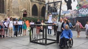 """2018年7月12日多個人權團體在巴黎蓬皮杜文化中心附近廣場上集會,紀念中國諾貝爾和平獎得主劉曉波逝世一周年。參加者最後牽手圍繞王克平作品""""空椅子""""留影"""