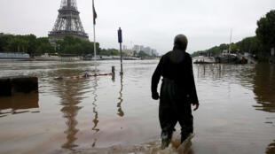 Homem caminha em rua inundada na beira do Sena, nesta sexta-feira (3).