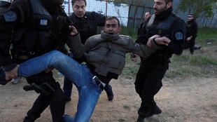 Des policiers interpellent un migrant lors d'affrontements près de Diavata, dans le nord de la Grèce, le 4 avril 2019.