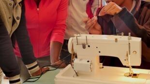 Les dix stagiaires découvrent les rudiments de la machine à coudre électrique, autour de l'une des formatrices, styliste transgenre.