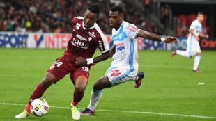 Metz midfielder Georges Mandjeck vies with Olympique de Marseille defender Henri Bedimo.