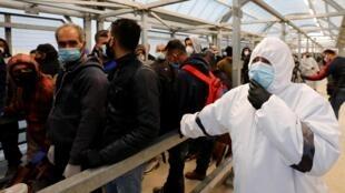 Un agent de santé observe les travailleurs palestiniens se rendre au travail en Israël à un poste de contrôle près d'Hébron en Cisjordanie occupée par Israël le 3 mai 2020.