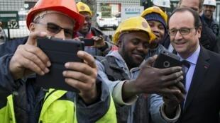 El presidente francés François Hollande se saca fotos junto a obreros.