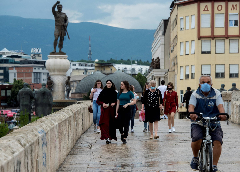 Des personnes portant des masques pour se protéger contre l'épidémie de Covid-19 passent devant une statue dans le centre de Skopje le 17 juin 2020.