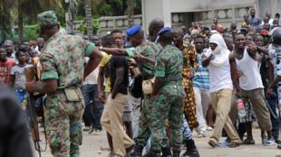Des soldats face aux habitants du quartier de Gobélé qui manifestent contre la destruction de leurs habitations. Cocody, le 22 juillet 2014.
