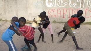 Des jeunes garçons pratiquent la lutte traditionnelle dans une rue de Kaolack, au Sénégal.