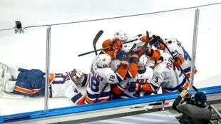 New York Islanders goaltender Semyon Varlamov, left, slides head first into a pack of teammates celebrating Jordan Eberle's game-winning goal in double overtime against the Tampa Bay Lightning in the Eastern Conference final series