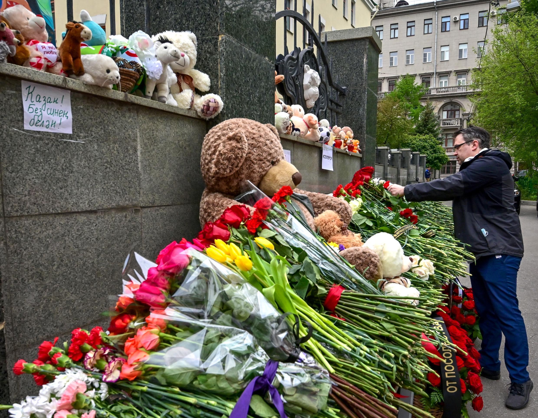 Un hombre coloca flores en homenaje a las víctimas del tiroteo en una escuela de Kazán, en el centro de Rusia, el 12 de marzo de 2021 en Moscú