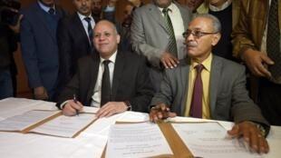 Ewade Abdesadek (g), président de la délégation du Congrès national (Tripoli), et Ibrahim Fethi Amish, du Parlement reconnu par la communauté internationale, signent des documents en vue d'un accord dans la banlieue de Tunis, le 6 décembre 2015.