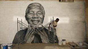 Cap Verdean Nelson Tavares paints a tribute to Mandela on a wall in Lisbon last year