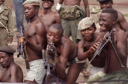 Des enfants soldats jouant avec des fusils d'assault AK-47.