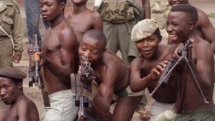 Des enfants soldats jouant avec des fusils d'assault AK-47 en RDC.