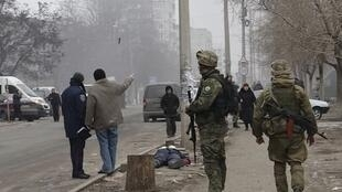 Des militaires ukrainiens en faction dans une rue de Marioupol, près du corps d'une vicitime des bombardements, le 24 janvier 2015.