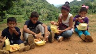 Niños del colegio María May comiendo lo que probablemente será el único plato del día.