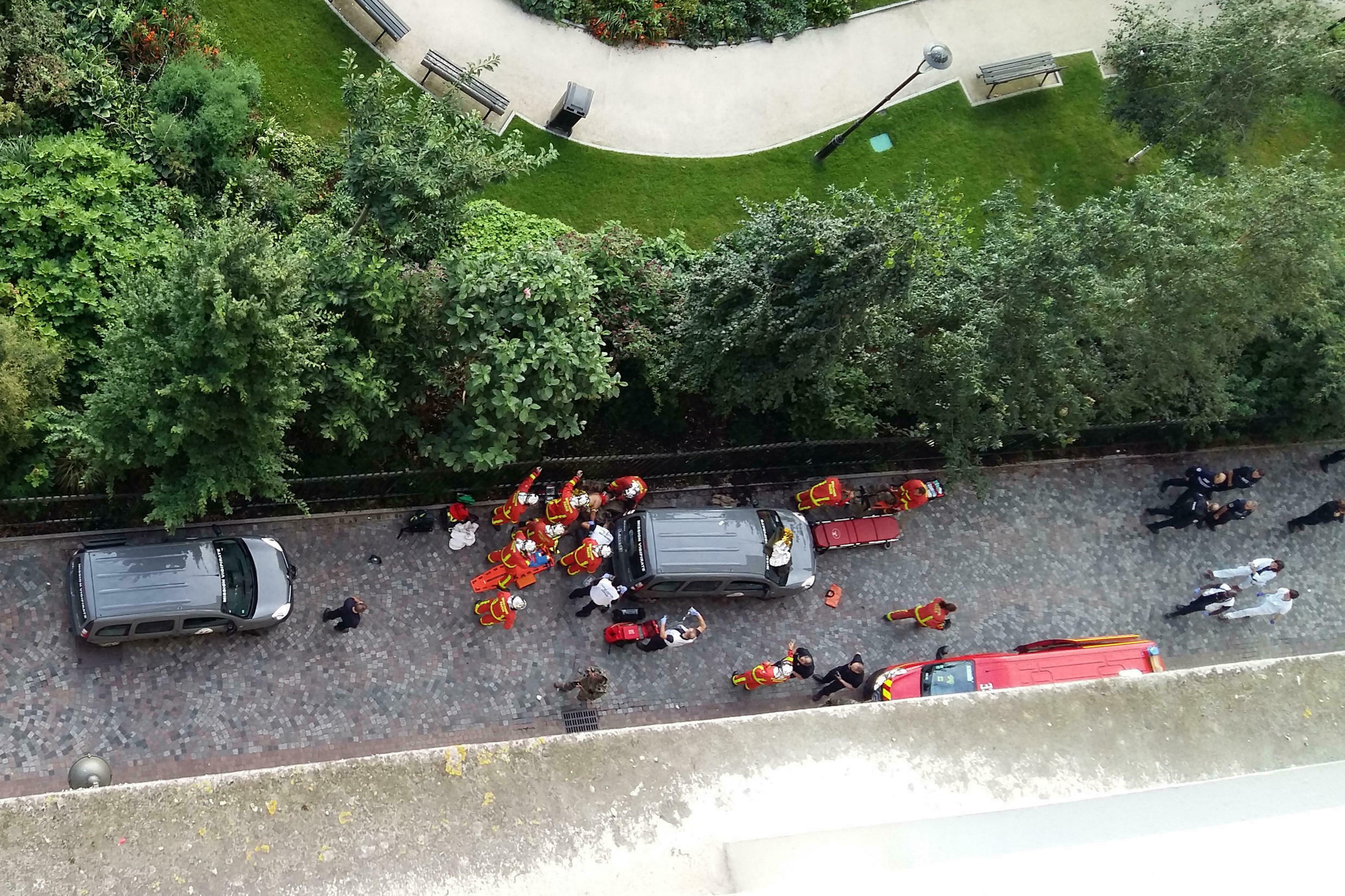 Officials and rescuers gather near vehicles after a car slammed into soldiers on patrol in Levallois-Perret, outside Paris on Wednesday.