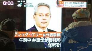 东京过路人看电视屏幕上报道日产前董事交保获释   2018年12月25日