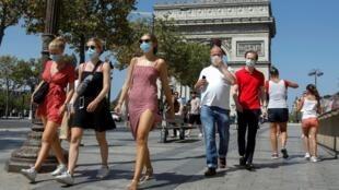Des passants près de l'Arc de Triomphe portent des masques, ce mercredi 12 août, alors que la France renforce les mesures pour enrayer une résurgence de l'épidémie de coronavirus à travers le pays.