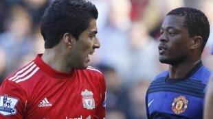 Dan wasan Liverpool Luis Suarez a gefen hagu tare dan wasan Manchester United Patrice Evra suna kallon juna a lokacin wasan Premier a filin wasa na Anfield. lokacin da Evra yace Suarez ya zage shi