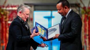 Le Premier ministre éthiopien Abiy Ahmed (d.) récompensé par le président du comité Nobel Berit Reiss-Andersen à l'hôtel de ville d'Oslo en Norvège, le 10 décembre 2019.