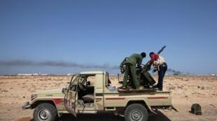 Rebeldes instalam metralhadora em sua pick-up, perto da refinaria de Ras Lanuf, recuperada pelos insurgentes neste domingo.
