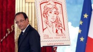 Le président François Hollande lors de la présentation du nouveau timbre, le 14 juillet 2013.