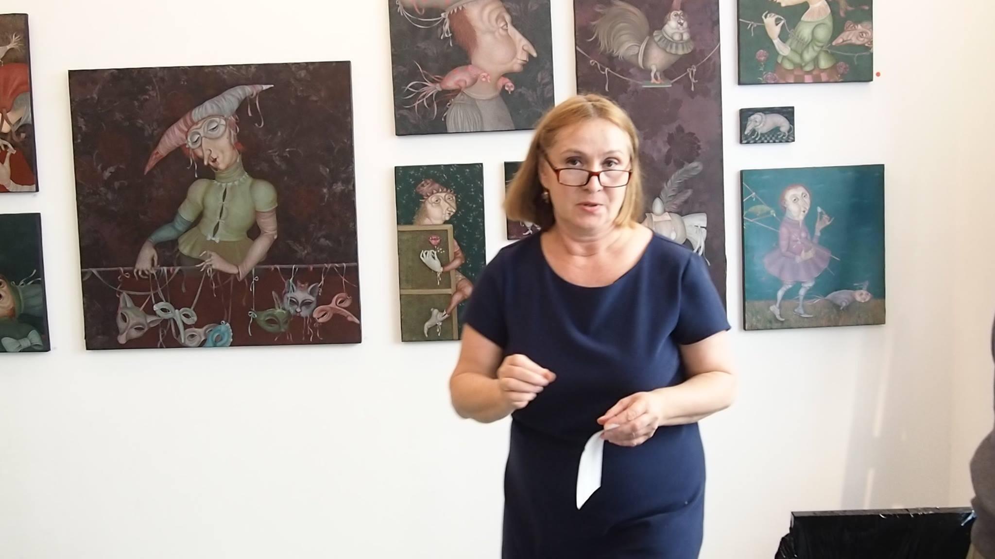 Ольга Хлопова в галерее на Монмартре на фоне работ художницы Евгении Саре