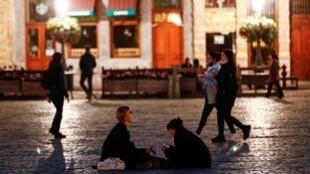 Deux jeunes assis sur la Grand-Place de Bruxelles, le 19 octobre. La Belgique est contrainte d'étendre son couvre-feu.