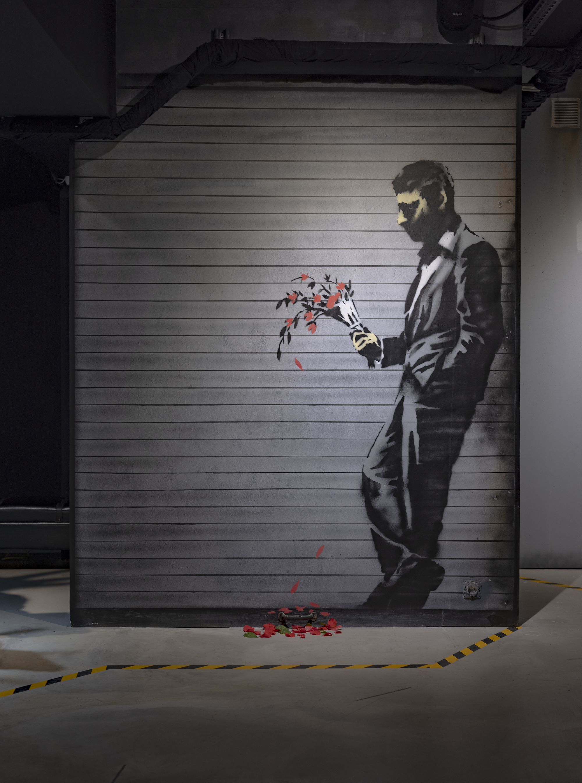 """Waiting In Vain… at the door of the club"". Banksy dropped this image of a man waiting with his red fading flowers on the streets of New York City in 2013."