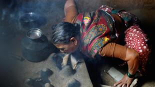 Mmoja wa wanawake nchini India akipuliza moto, hizi ni kazi ambazo UN inasema wanawake wanaishia kuzifanya