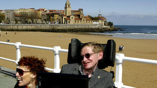 British astrophysicist Stephen Hawking (R) and his wife Elaine pose in front of the San Lorenzo beach in the northern Spanish city of Gijon April 10, 2005.