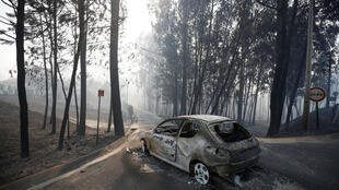 A burned car is seen in the aftermath of a forest fire near Pedrogao Grande, in central Portugal, June 18, 2017.