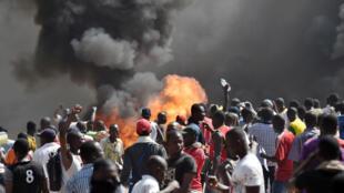 Manifestants devant l'Assemblée nationale en feu à Ouagadougou, Burkina Faso, le 30 octobre 2014.