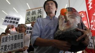 Nhà hoạt động chính trị Avery Ng cầm một chiếc mặt nạ có hình ông Lương Chấn Anh (REUTERS)