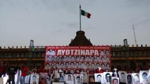 Les portraits des étudiants disparus à Iguala en septembre 2014 sont brandis par la foule le 26 janvier 2015 à Mexico.