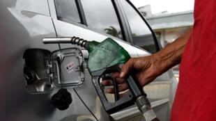Un employé travaille dans une station-service à Caracas le 30 juillet 2018. Le président vénézuélien, Nicolas Maduro, a annoncé la réglementation du prix de l'essence pour l'essence la moins chère au monde, grâce à l'utilisation du «carnet de la patria».