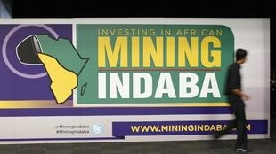 Delegates walk past a sign at the start of the Investing in Africa Mining Indaba in Cape Town