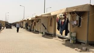 Residents hang their laundry out in front of their container, Elbeyli refugee camp.