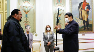Venezuelan President Nicolas Maduro (R) holds the sword given to him US actor Steven Seagal