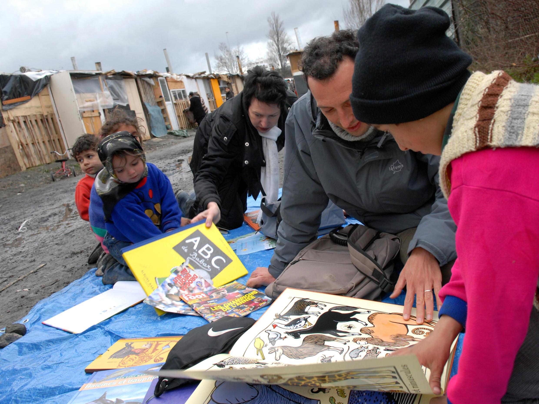 Des bénévoles d'ATD Quart Monde France animent une bibliothèque de rue pour des enfants roms.