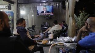 Des Libanais écoutent l'allocution du président Michel Aoun à la télévision, à l'occasion du troisième anniversaire de son accession à la présidence, dans un contexte de forte contestation sociale, à Beyrouth, le 31 octobre 2019.